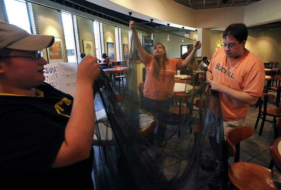 From left, Christy Monroe, Tiffany Tadlock and Joshua Hale unravel a mosquito net in Lamar's Setzer Student Center on Thursday, October 6, 2008. Hale will be traveling to Africa to deliver the nets to malaria stricken areas. Guiseppe Barranco/The Enterprise