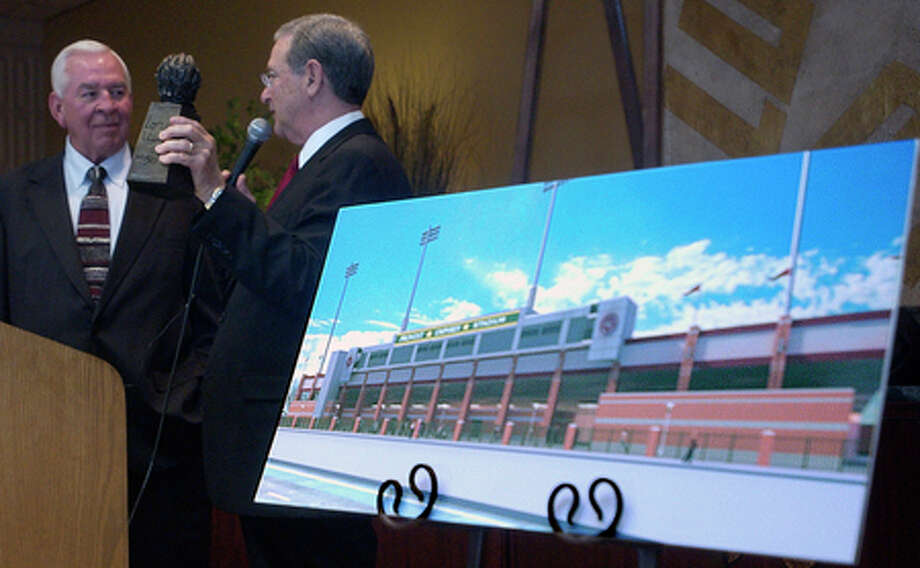 Walter Umphrey, left, accepts a statue from Lamar University President Jimmy Simmons, right, after the announcement of a $4 million total contribution to the football program.  The Provost Umphrey Law Firm gave $3 million, and Walter and his wife Sheila gave $1 million to Lamar and the football stadium now will be known as Provost Umphrey Stadium.   Dave Ryan/The Enterprise