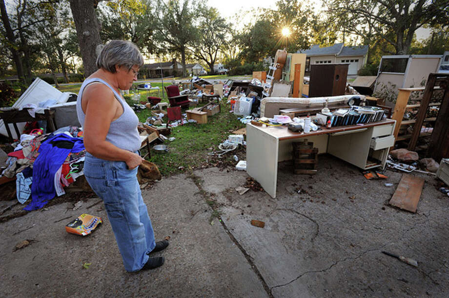 Janice Cox walks through her driveway looking over the contents of her home that were damaged from flood waters of Hurricane Ike. Guiseppe Barranco/The Enterprise