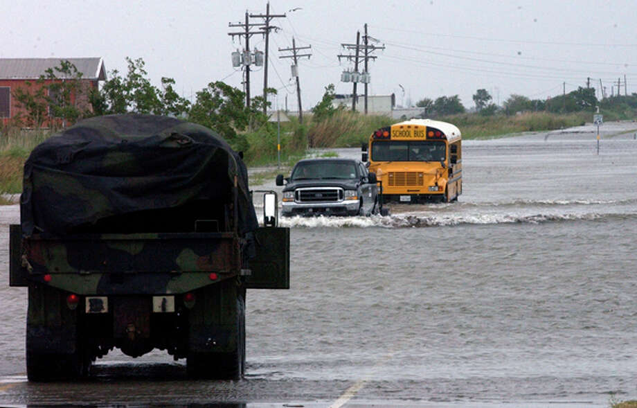A school bus follows a 4 wheel drive truck through the waters covering Texas 87 to Sabine Pass Friday morning.  Dave Ryan/The Enterprise