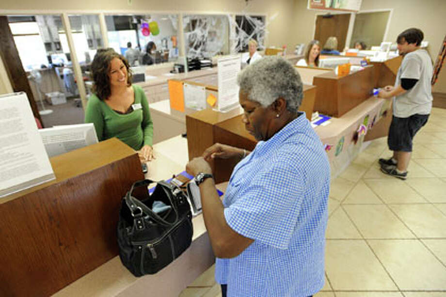 Dupont Goodrich Federal Credit Union teller, Melinda Rennick, left, helps Jessie Lamb, right, complete a transaction at the branch on Eastex Freeway. Monday, October 20, 2008. Valentino Mauricio/The Enterprise