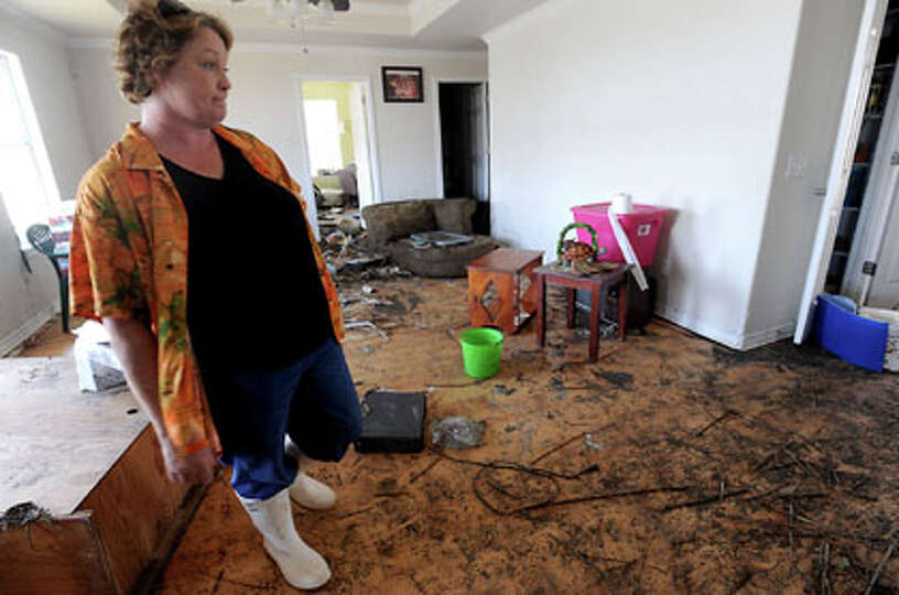 Lorrie Seymour talks about the damage to her home in Sabine Pass, Tuesday. Tammy McKinley/The Enterp