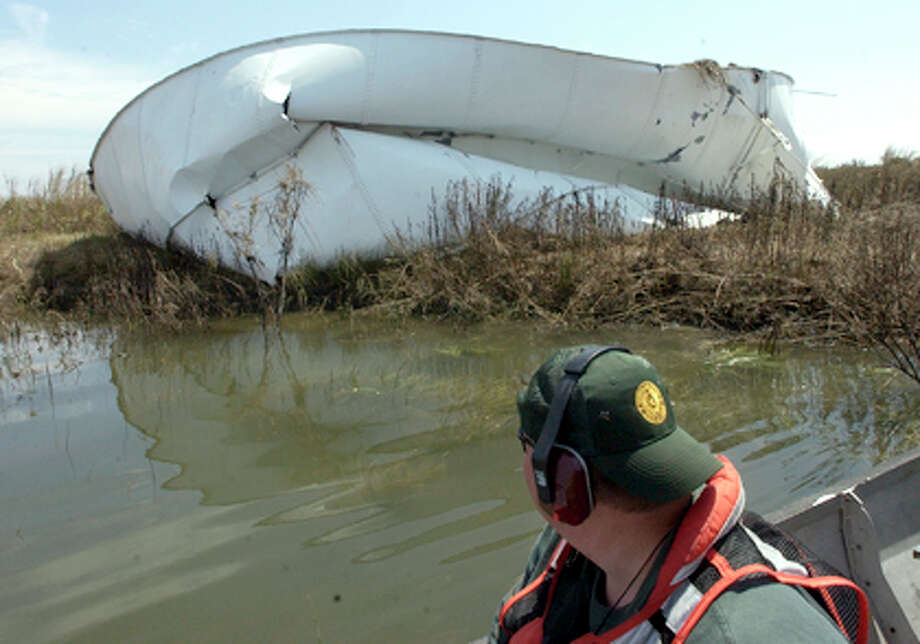 Johnny Darcey, a Response Officer with the Texas General Land Office Oil Spill Division, who on Wednesday, was surveying  the damage to a Papco pumping and storage facility on Clam Lake, came across one of the storage tanks north of the Intercostal Waterway.     Dave Ryan/The Enterprise