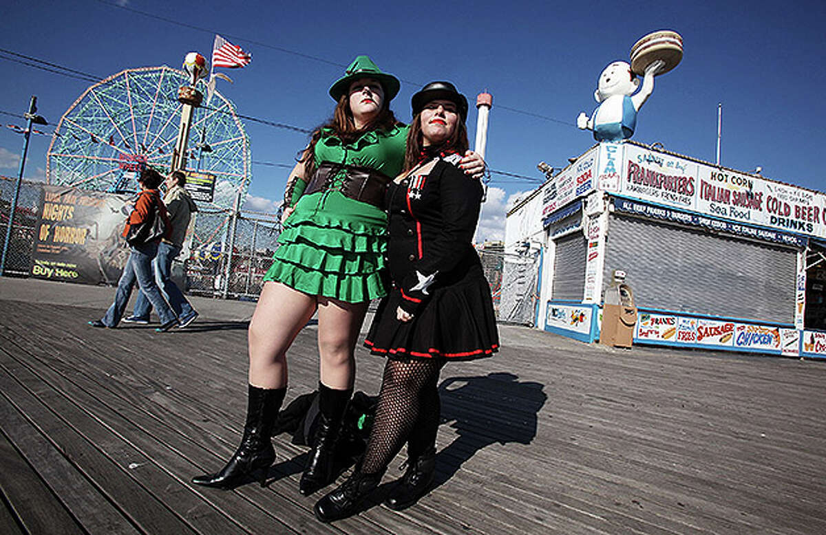 NEW YORK - OCTOBER 31: Costumed revelers Emily Morin (L) and Tara Eres pose on the boardwalk at historic Coney Island on Halloween October 31, 2010 in the Brooklyn borough of New York City. Revelers across the country are celebrating Halloween the day before the Christian tradition of All Saints' Day which honors the dead. (Photo by Mario Tama/Getty Images)