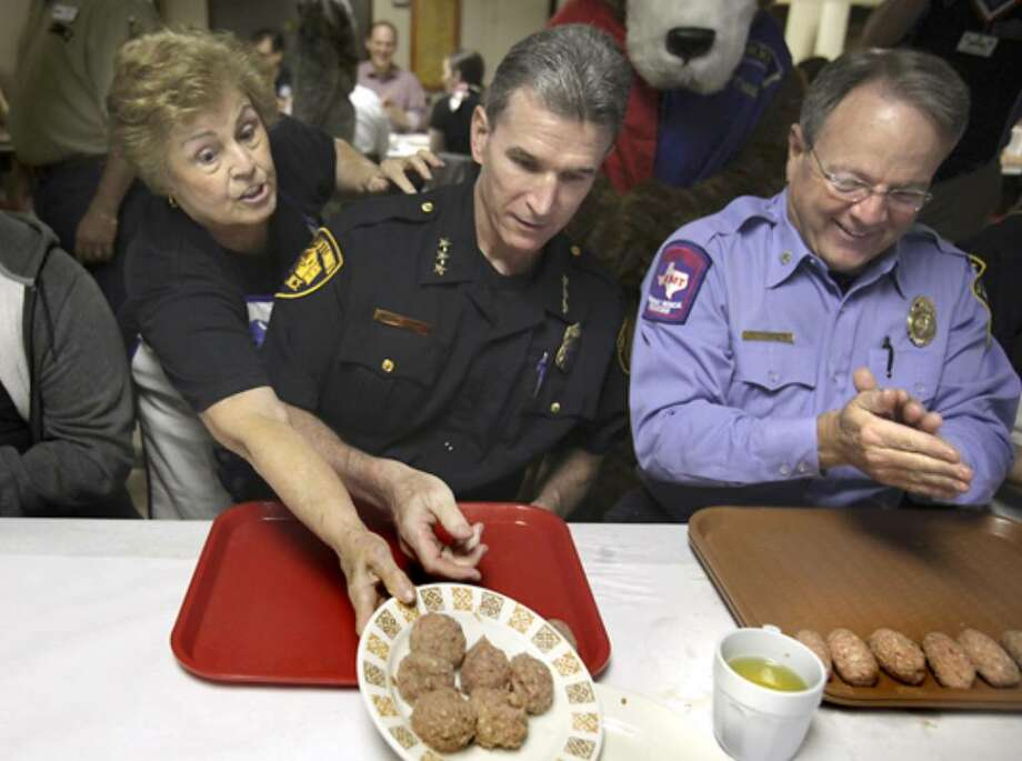 Retiring SAFD Battalion Chief Tommy Thompson (far right) helped SAPD Chief William McManus make meatballs for a benefit earlier this month.