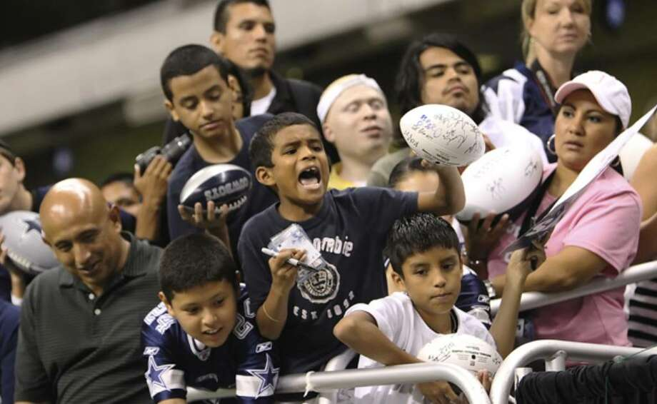 A young fan tries to get more signatures on his autographed football.
