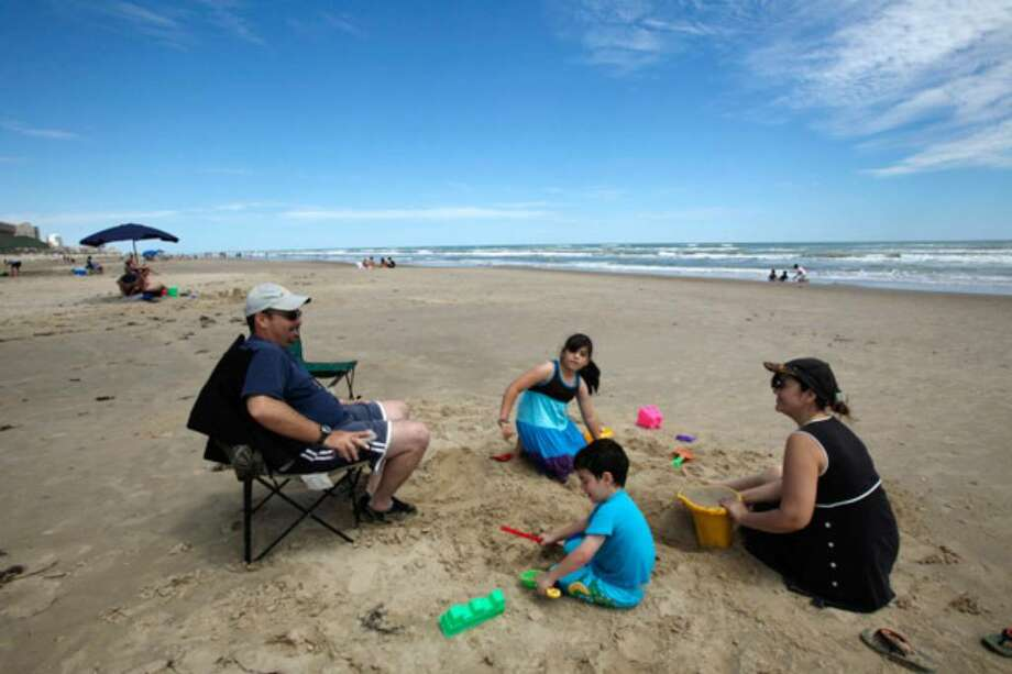 The Reza family from Monterry, Mexico, enjoy the beach at South Padre Island in 2009. Before hitting the beach — or anywhere else — this summer, perform a few tasks to give your home an energy break while you're gone.