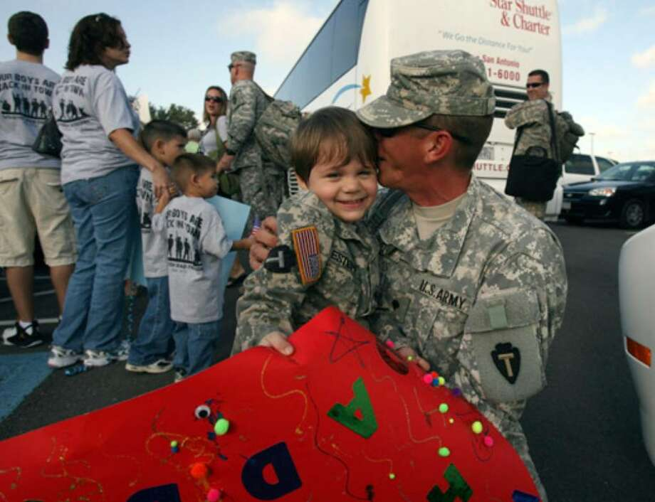 Spc. Kevin Estepp (right) greets 3-year-old son Justin. Estepp returned to San Antonio from Iraq with about 150 other members of the National Guard.