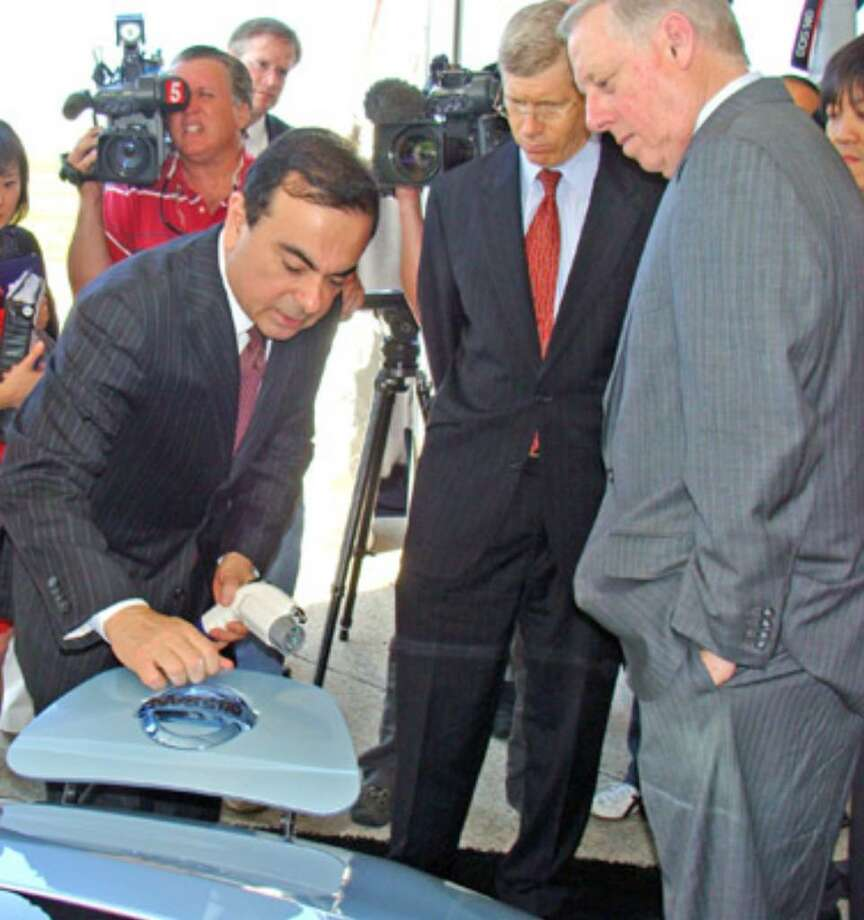 Nissan President and CEO Carlos Ghosn connects a charger to the front of a Nissan Leaf electric car during the recent groundbreaking ceremony for the lithium-ion battery plant at the Smyrna, Tenn., manufacturing complex.