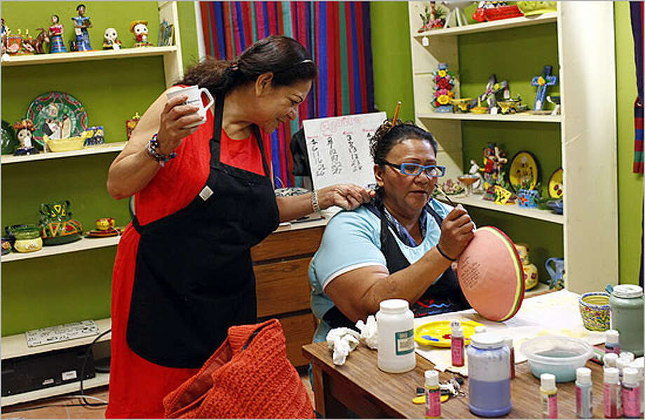 Coordinator Imelda Arizmendez (left) looks at the earrings worn by Grace Gonzalez while Gonzalez paints the rim of a bowl at MujerArtes, the Esperanza Center's women's clay co-op.