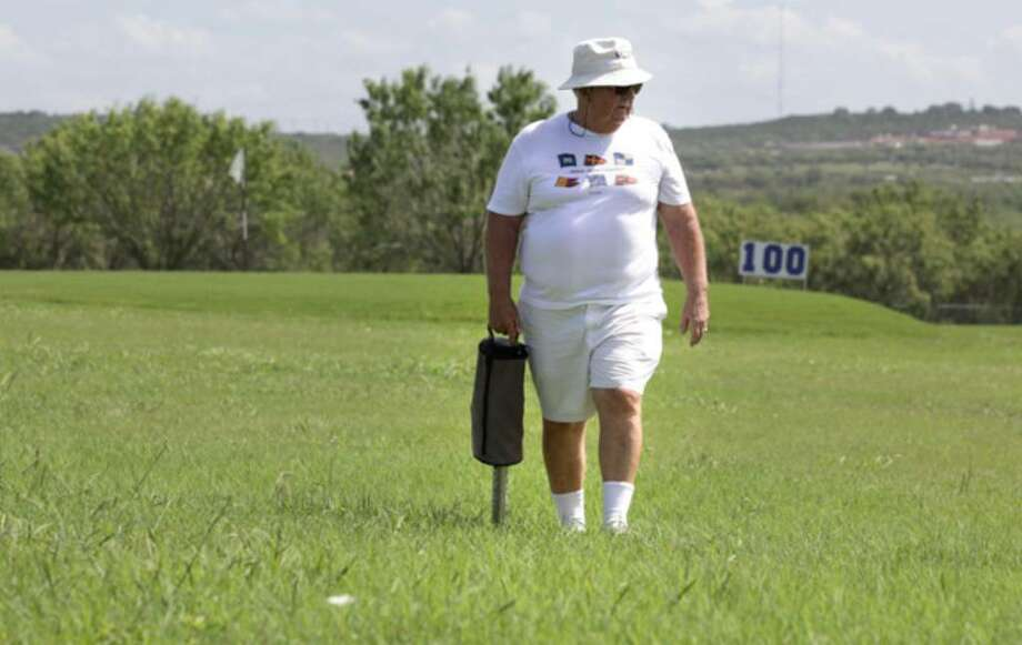 Retired Brig. Gen. Marc McClelland carries a shag bag after hitting balls Tuesday at the driving range at Air Force Village. He says he enjoys the exercise of retrieving golf balls and tends to bring back more than he hits.