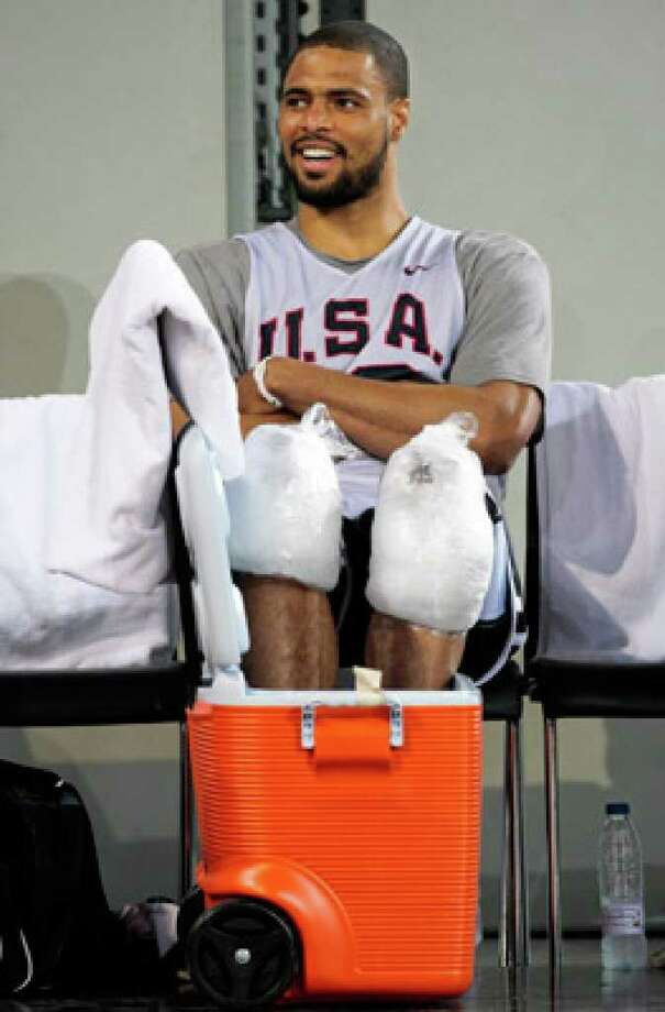 U.S. center Tyson Chandler, the team's only 7-footer, cools off his feet and knees with ice after a training session in Madrid.