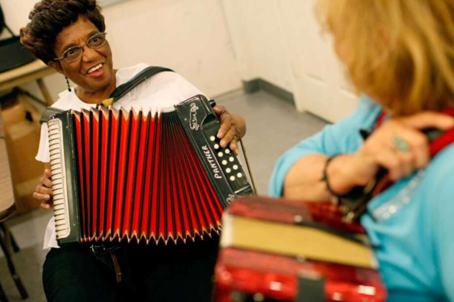 Gloria Gafford (left) gets advice from instructor Rita Del Rio during the free accordion classes for seniors at the Bethel Senior Nutrition Center.