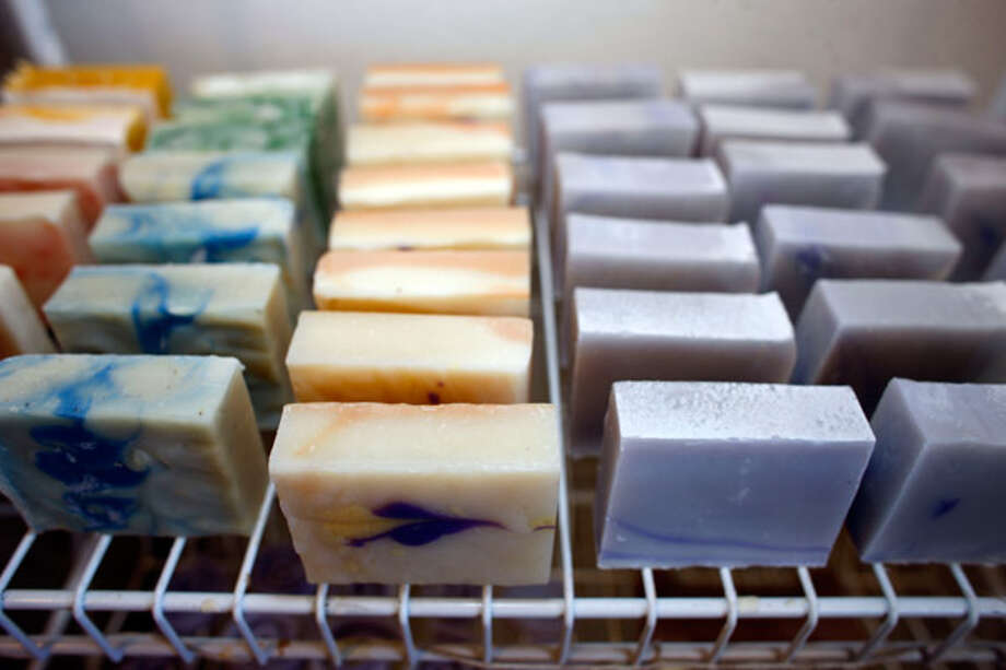 Bars of soap are shown sitting in racks for six weeks of curing after they were made by Lindsey Mann for her to sell at craft fairs and farmers markets.