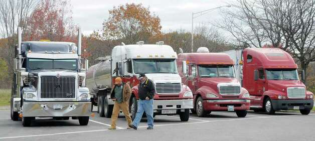 Truckers Butch Savage, lef, from Fultonham, N.Y., and David Bass, right, from Cape Coral, Fla., talk outside their trucks  at the Schodack Interstate 90 rest stop in Schodack, N.Y. on Monday, Nov. 1, 2010.  Savage's son-in-law was trucker, Jason Rivenburg, who was murdered in his truck while on a trip in South Carolina.  Rivenburg  was spending the night in the lot of an abandoned gas station when he was shot.   (Paul Buckowski / Times Union) Photo: Paul Buckowski / 00010889A