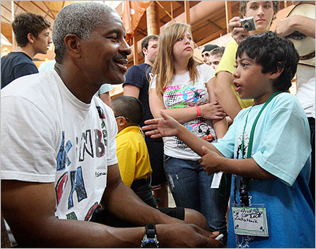 Former Dallas Cowboys player Everson Walls talks with camper Zach Gutierrez, who was attending Camp Reynal at Camp John Marc in Meridian.