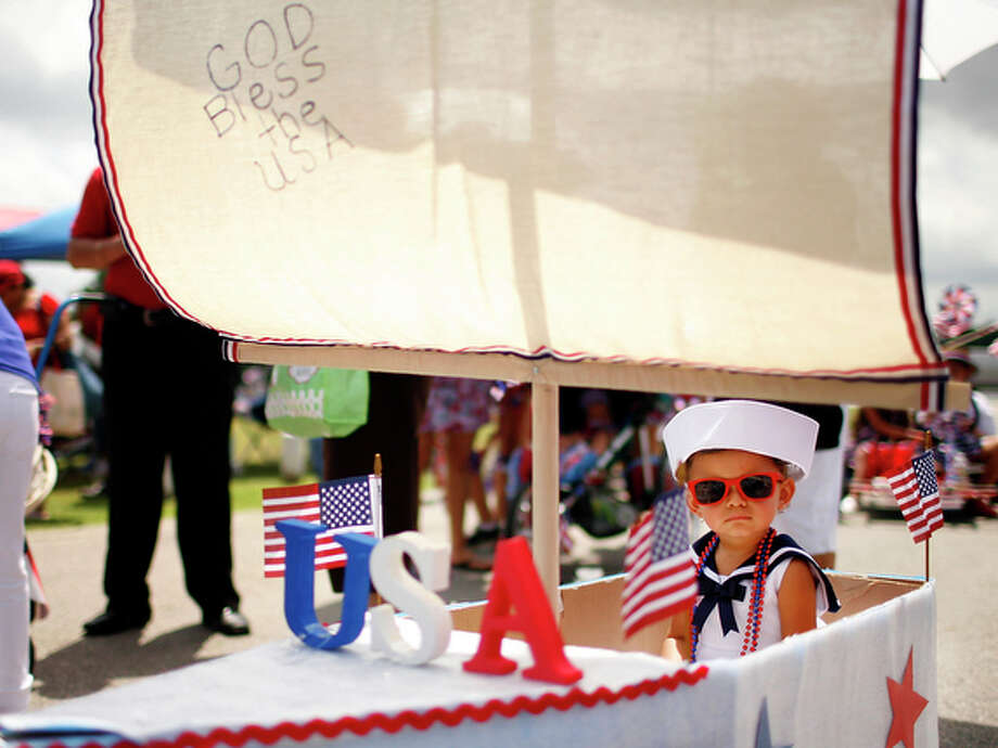 Olivia Meras, 22-months, plays with Georgio during the Woodlawn Park Lake Kids Parade on July 4, 2010. / iaguirre@express-news.net
