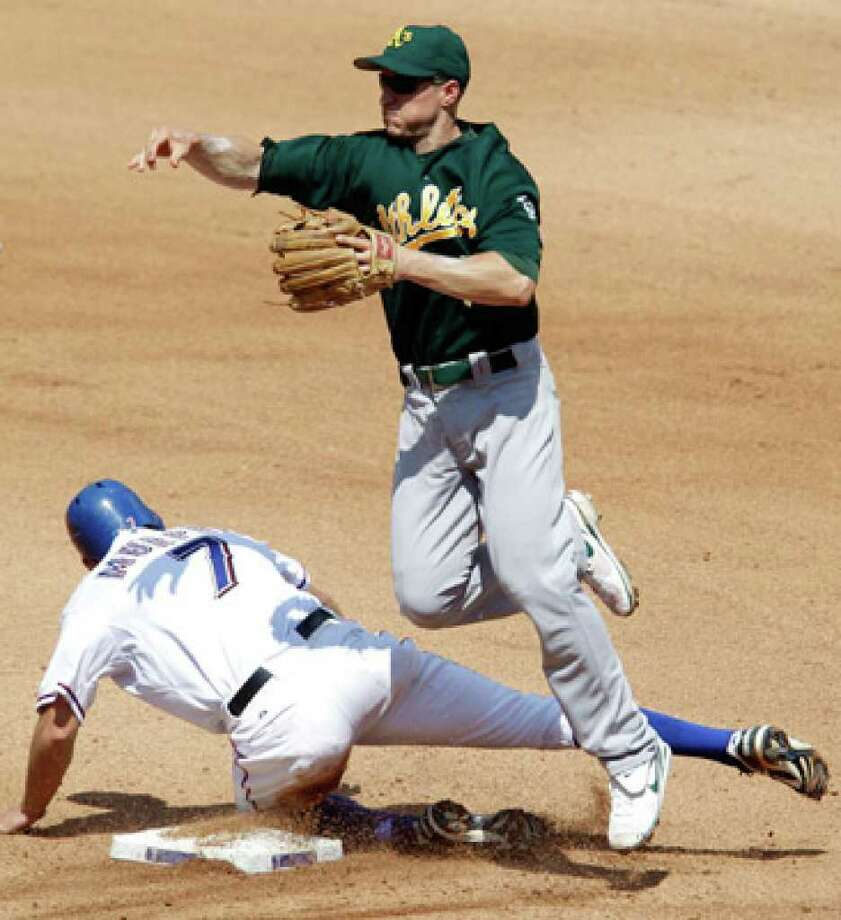 Athletics second baseman Mark Ellis (top) makes the throw to first for the double play after forcing the Rangers' David Murphy at second. Bengie Molina was out at first.