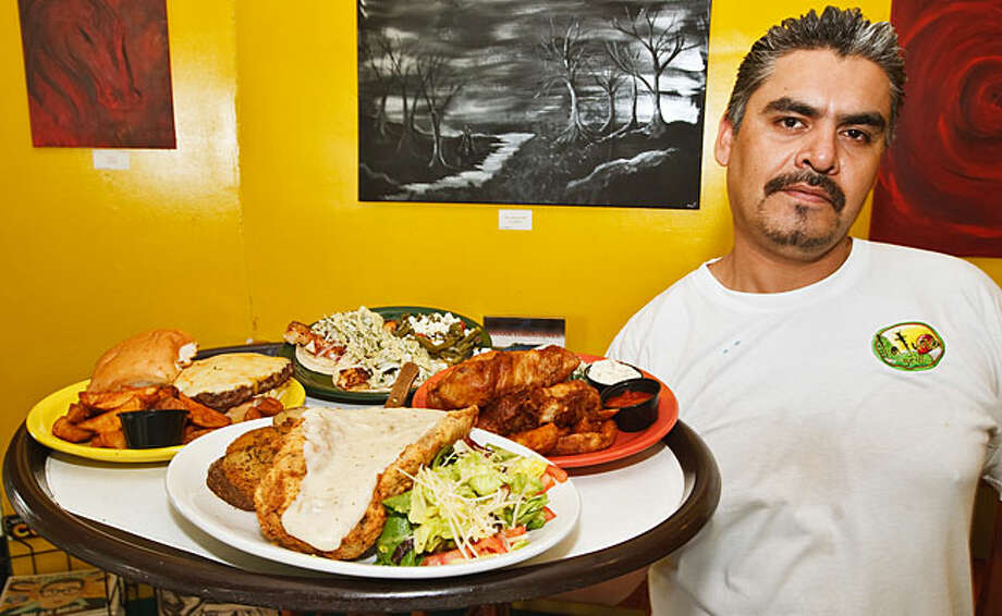 Mario Huerta carries a tray of food to customers at La Tuna Grill, 100 Probant St. / Prime Time Newspapers 2010