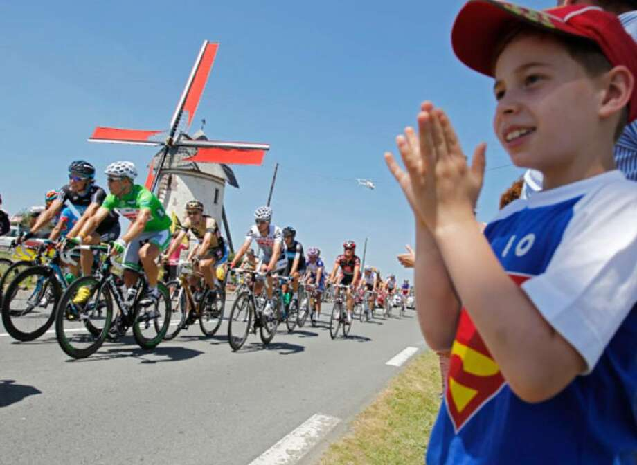 A boy applauds as the pack, including Norway's Thor Hushovd (in green), passes a windmill near Cambrai, France.
