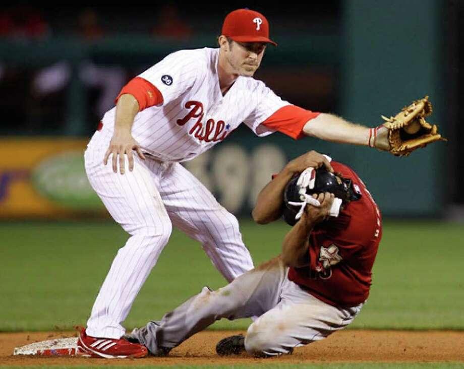 Houston Astros second baseman Anderson Hernandez beats Philadelphia Phillies second baseman Chase Utley's tag at second.