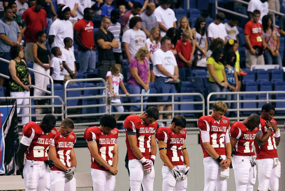 Players from the South Team bow their heads in prayer before the start of the Texas High School Coaches Association All-Star football game at the Alamodome on Tuesday, July 20, 2010. / San Antonio Express-News