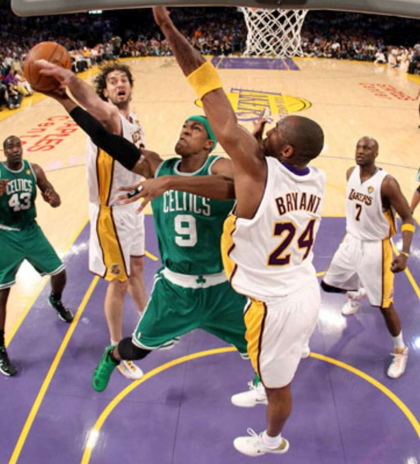 Boston Celtics guard Rajon Rondo (9) goes to the rim as the Lakers' Pau Gasol (left) and Kobe Bryant defend.