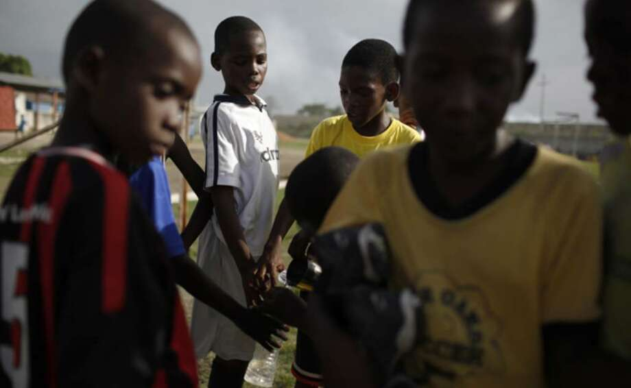 Children break for water during a free soccer clinic in Port-au-Prince, the capital of Haiti devastated by the January earthquake, on June 10.