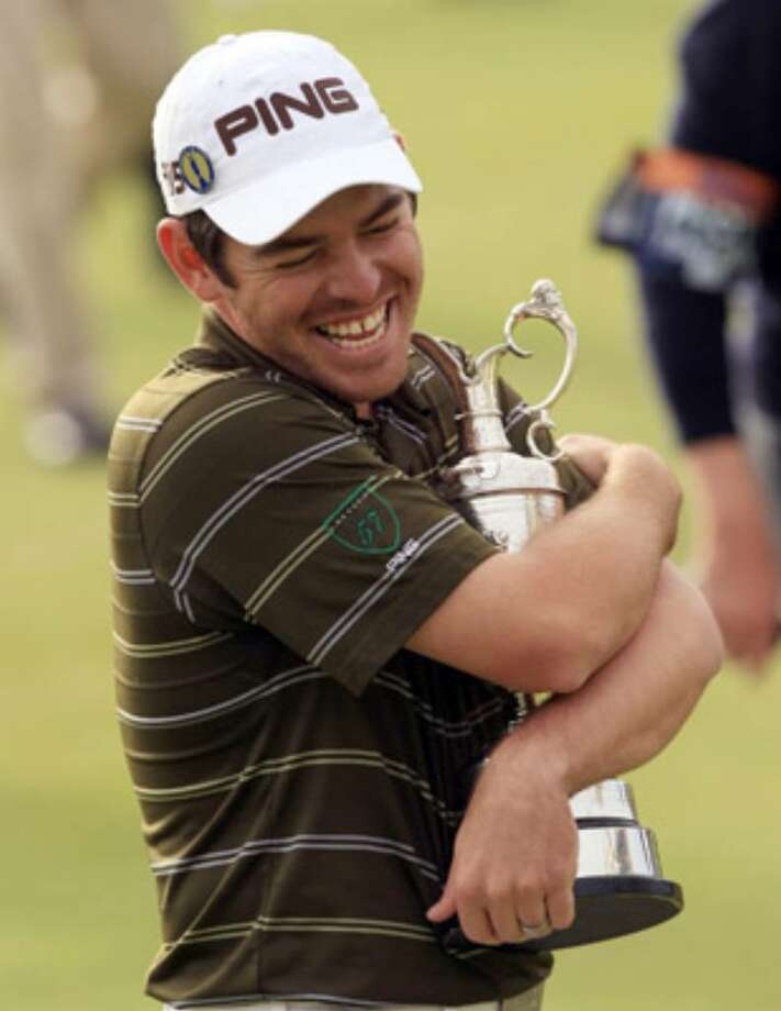 South Africa's Louis Oosthuizen cradles the claret jug Sunday. His 16-under 272 was good for a seven-shot victory in the British Open at St. Andrews, Scotland.