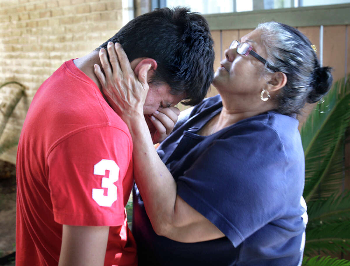 Alejandro Perez (left), whose twin sister Alejandra was killed, is comforted by neighbor Carrie Perez (right).