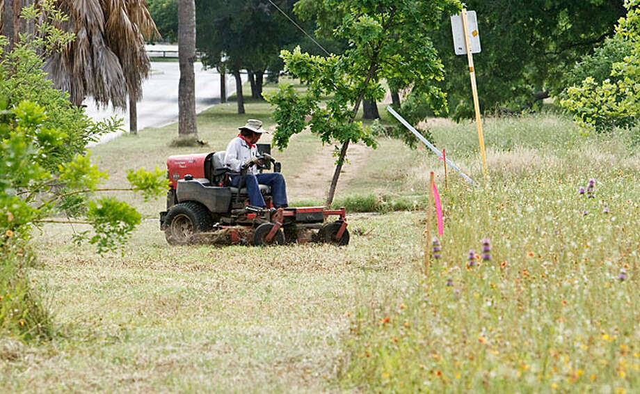 A city worker mows along Funston Place in Mahncke Park on May 21. The San Antonio Parks and Recreation Department, by the Mahncke Park Neighborhood Association's request is not mowing wildflowers in the park's interior. / Prime Time Newspapers 2010