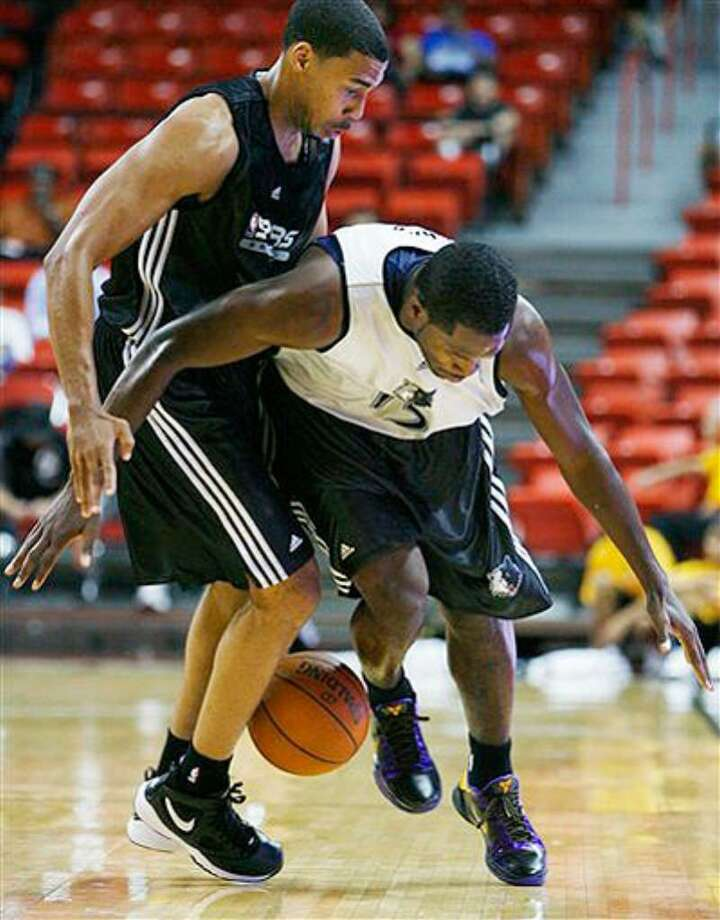 Minnesota's Jeremy Pargo (right) loses the ball while guarded by the Spurs' Garrett Temple on Monday. An ankle injury will likely sideline Temple for the rest of summer-league play.