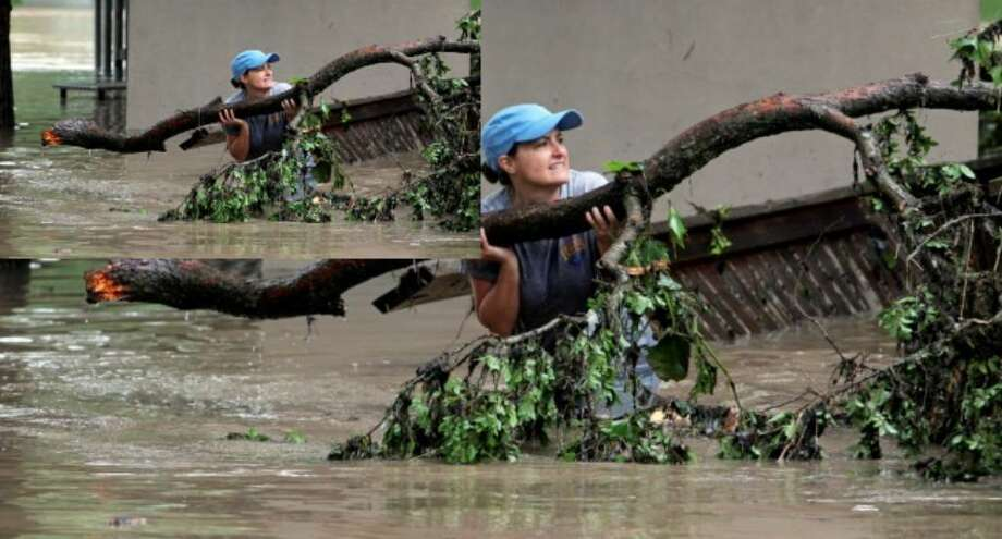 With a warning that waters could go higher, Kris Bostow struggles to get debris off her fence and property along the Guadalupe River at Lake Dunlap Tuesday.