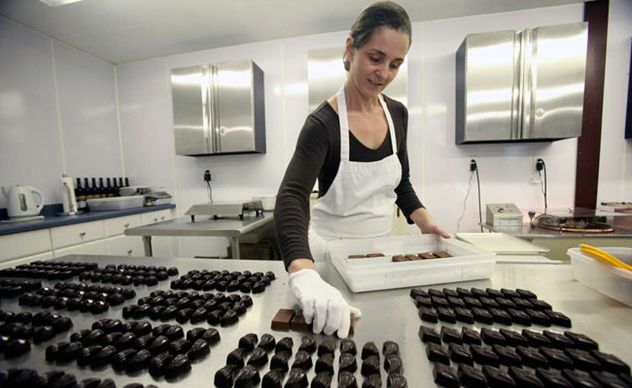 Assistant chocolatier Tia Niehus sorts the finished pieces, which feature ganache in a variety of flavors inside a solid dark chocolate coating. / © 2010 San Antonio Express-News