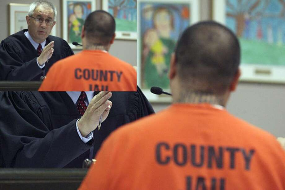 Associate Judge James Rausch speaks with a Bexar County Jail inmate during a hearing at the Bexar courthouse. Some inmates are allowed to go home to begin chipping away at their back payments.
