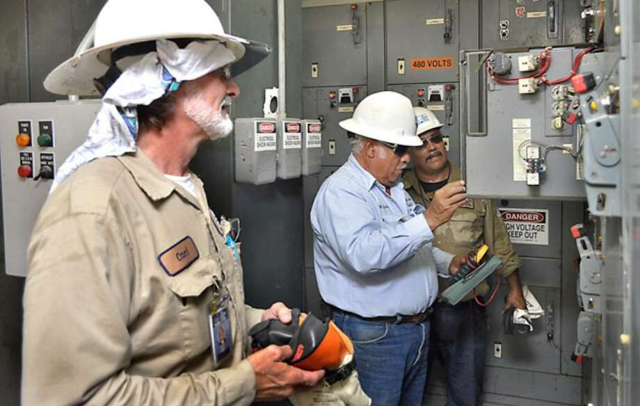 SAWS employees Carl Ehert (from left) and Richard Villarreal work with Merced Galvan of the City of Laredo Utilities Division at a Laredo water treatment plant Monday.