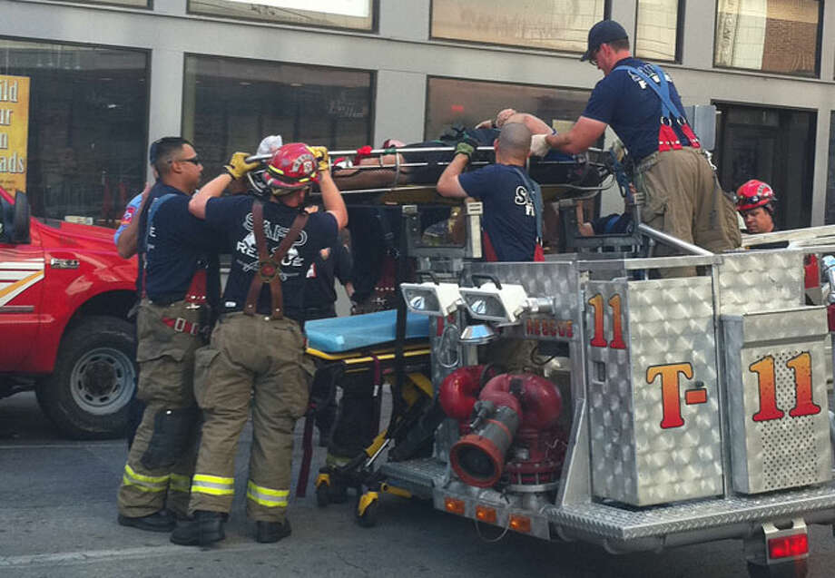 Firefighters rescue a policeman who broke his ankle while searching for a suspected copper thief on the roof of an abandoned building downtown Sunday morning.