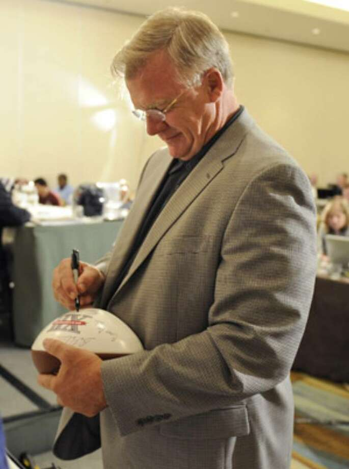 A&M coach Mike Sherman autographs a football before a news conference at Big 12 Football Media Day.