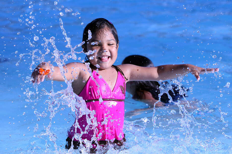 Mariah Martinez, 5, cools off in the Woodlawn Park pool as the temperature hit 100 degrees Sunday for the first time this summer, according to the National Weather Service.