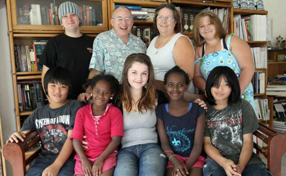 Martin and Debbie Adamo (back row, center) take a family photograph with their six children and foreign exchange student Sara Milic (front row, center) from Berlin, who lived with them for 10 months before returning to Germany on Monday.