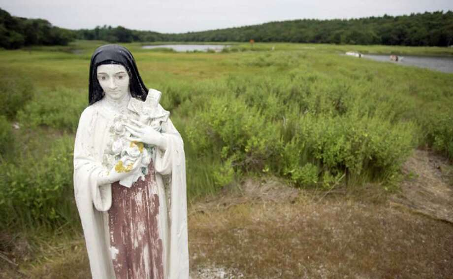 A statue of St. Therese resides on the retreat land of the Congregation of the Sacred Hearts of Jesus and Mary in Wareham, Mass. The order has sold development rights on about 100 acres of its property, which is now permanently preserved.