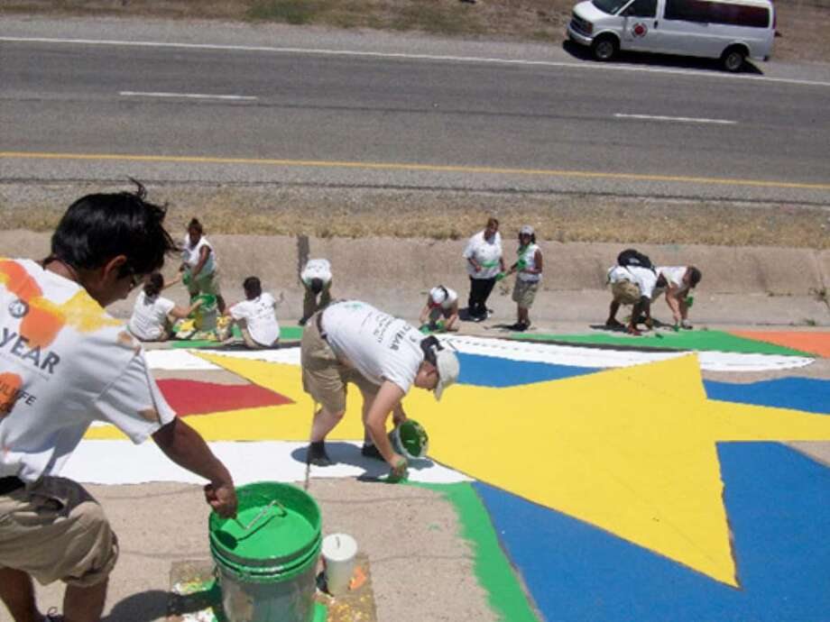 City Year member Lila Givens (center) paints on a mural along Loop 410 near Christa McAuliffe Middle School, where she works in a program to keep students from dropping out.