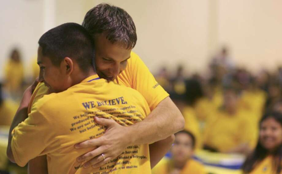 Mark Larson, head of KIPP San Antonio, hugs a student after presenting a medal during an eighth-grade ceremony in 2008.