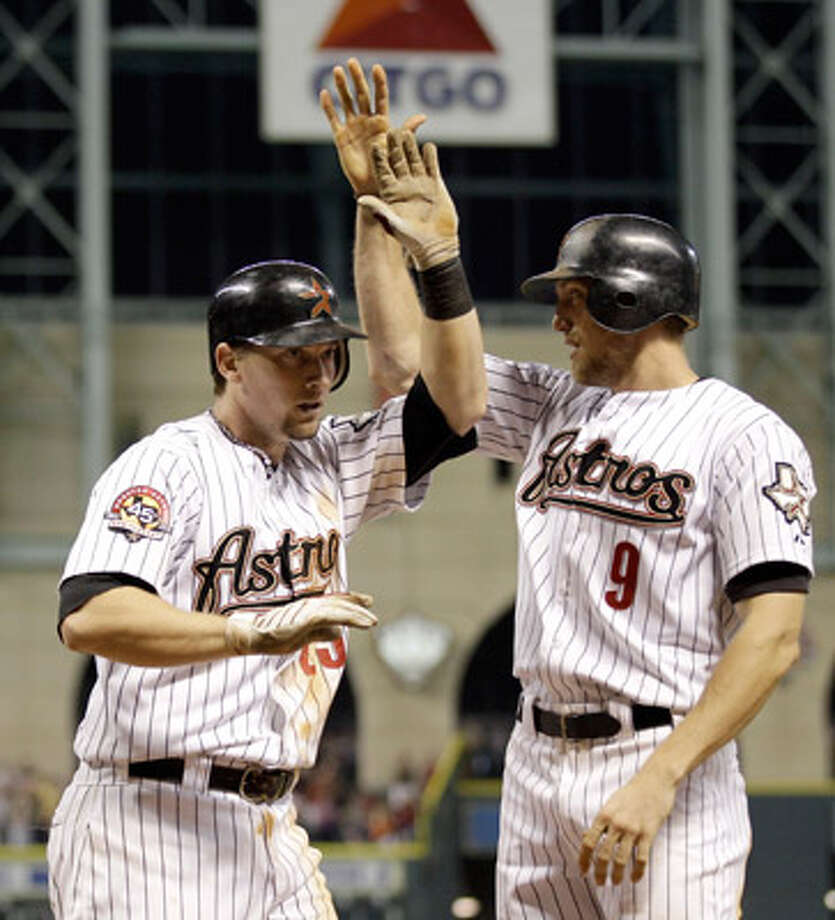 Houston Astros rookie Chris Johnson (left) is greeted by Hunter Pence after both scored on Johnson's single and a two-base error by Atlanta Braves catcher Brian McCann.