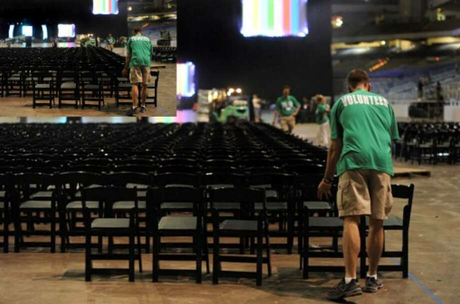 A volunteer places chairs on the floor of the Alamodome in preparation for the 2010 International Convention of Alcoholics Anonymous .