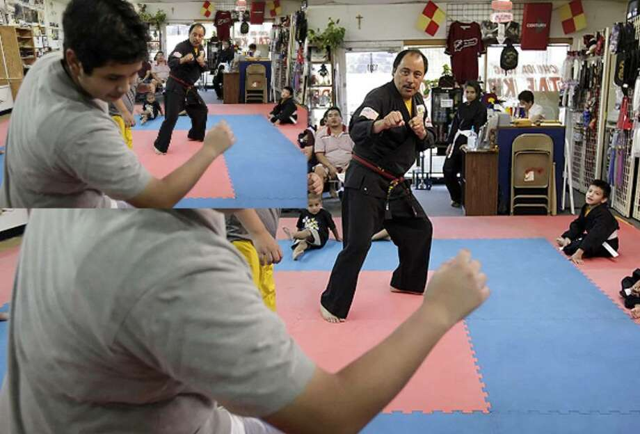 Martial arts instructor Jesse Rodriguez (right) watches as student Michael Rodriguez (no relation) takes a kick from his cousin Jason Garcia during a class at Golden Dragon Karate Studio on the city's West Side.