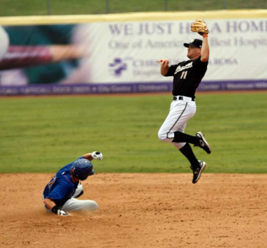 Missions second baseman Logan Forsythe leaps to catch a high throw as Tulsa's Charles Blackmon steals the base.