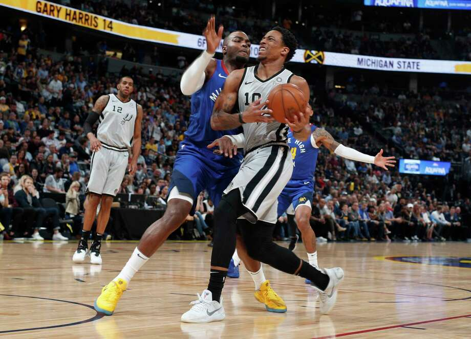 San Antonio Spurs forward Rudy Gay saves the ball from bouncing out of play as he runs into fans in the courtside seats in the first half of an NBA basketball game against the Denver Nuggets, Friday, Dec. 28, 2018, in Denver. (AP Photo/David Zalubowski) Photo: David Zalubowski, Associated Press / Copyright 2018 The Associated Press. All rights reserved.