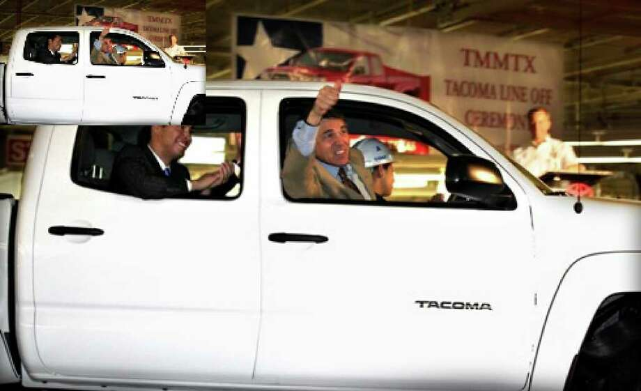 Texas Gov. Rick Perry gives thumbs up as he and San Antonio Mayor Julian Castro (left) ride in the first Tacoma truck as Toyota holds its TMMTX Tacoma Line-Off Ceremony Friday.