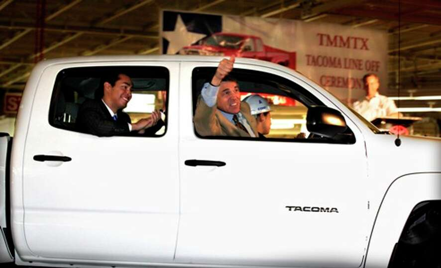 Texas Gov. Rick Perry gives thumbs up as he and San Antonio Mayor Julian Castro (left) ride in the f